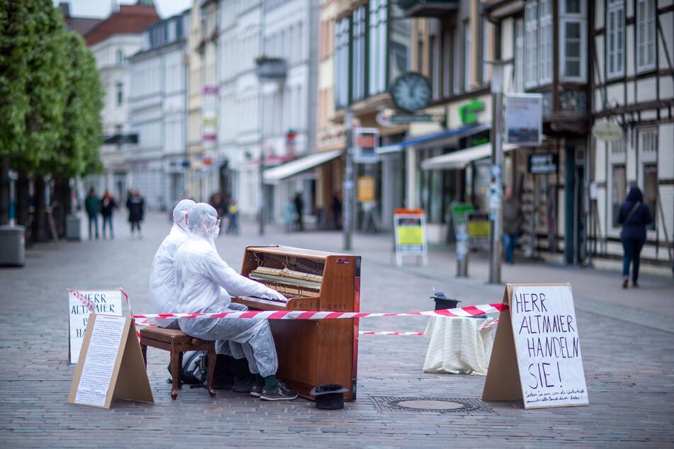 Zwei Musiker demonstrieren in Schwerin gegen die Regeln des Corona-Kulturfonds.