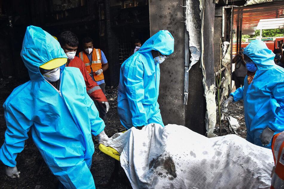 Mitarbeiter vom indischen Katastrophenschutz tragen den Leichnam eines Brandopfers aus einem Hotel im Bezirk Vijayawada, nachdem in einer dort eingerichteten Station zu Behandlung von Covid-19-Patienten ein Feuer ausgebrochen war.