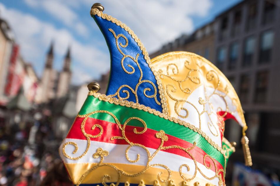 Ein Karnevalist trägt beim Faschingsumzug eine bunte Narrenkappe (Symbolfoto).