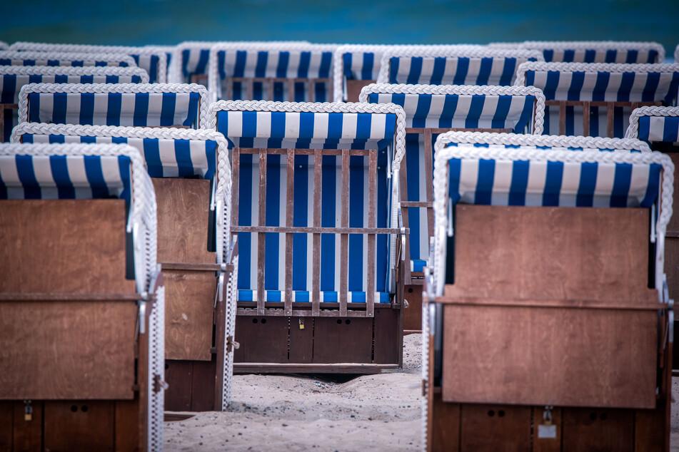Mecklenburg-Vorpommern, Rostock: Leere Strandkörbe eines Verleihers stehen am Strand von Warnemünde.