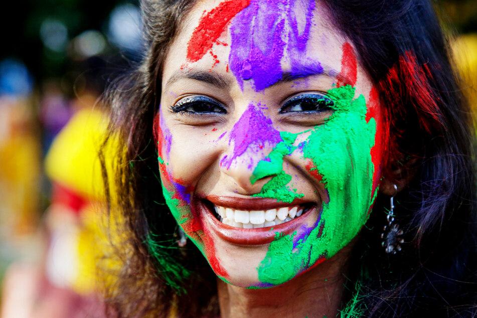 Eine mit Farbe bemalte Frau lächelt während des Holi-Festes in Kalkutta, Indien.