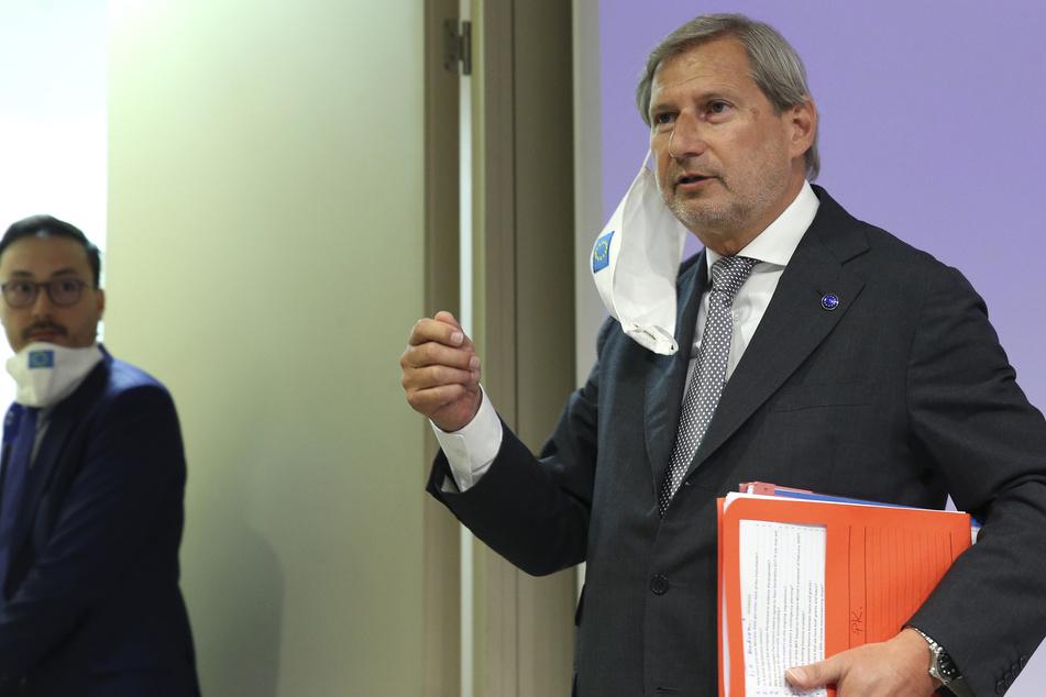 Johannes Hahn (r), EU-Kommissar für Haushalt und Verwaltung, trägt eine Stoffmaske mit aufgenähter Europäischer Flagge um ein Ohr gehängt, als er eine Pressekonferenz im EU-Hauptquartier verlässt. Die EU-Kommission präsentierte am Mittwoch einen Corona-Wiederaufbauplan. Es sollen 750 Milliarden Euro für die wirtschaftliche Erholung Europas nach der Corona-Krise mobilisiert werden.