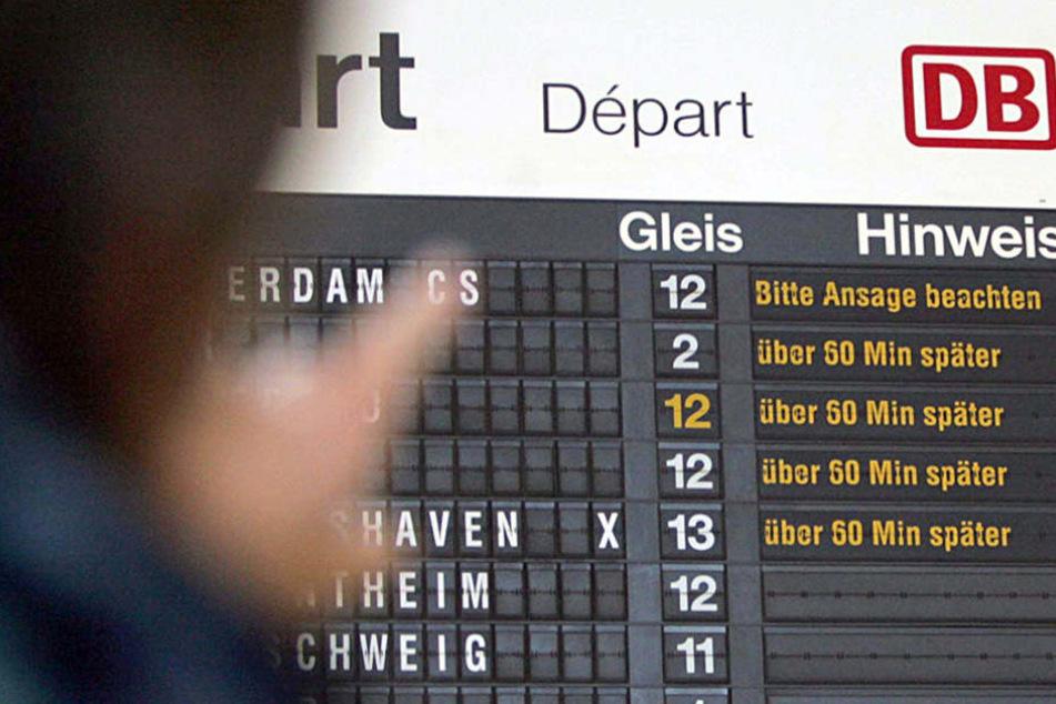 Ein Reisender betrachtet im Hauptbahnhof von Osnabrück eine Anzeigentafel, die die Verspätungen im Zugverkehr anzeigt.