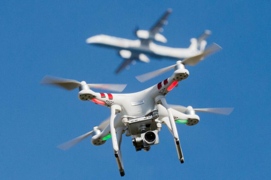 Eine Drohne mit einem Flugzeug im Hintergrund.