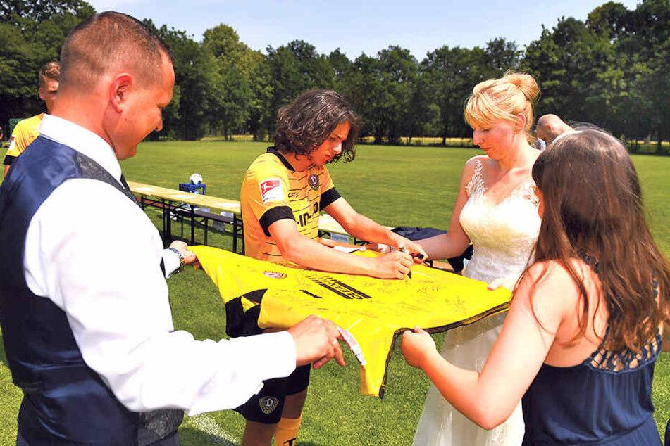 Nach dem Mannschaftsfoto signierten die Spieler, hier Matthäus Taferner, ein großes Dynamo-Trikot für Cindy und Robin Kühne.