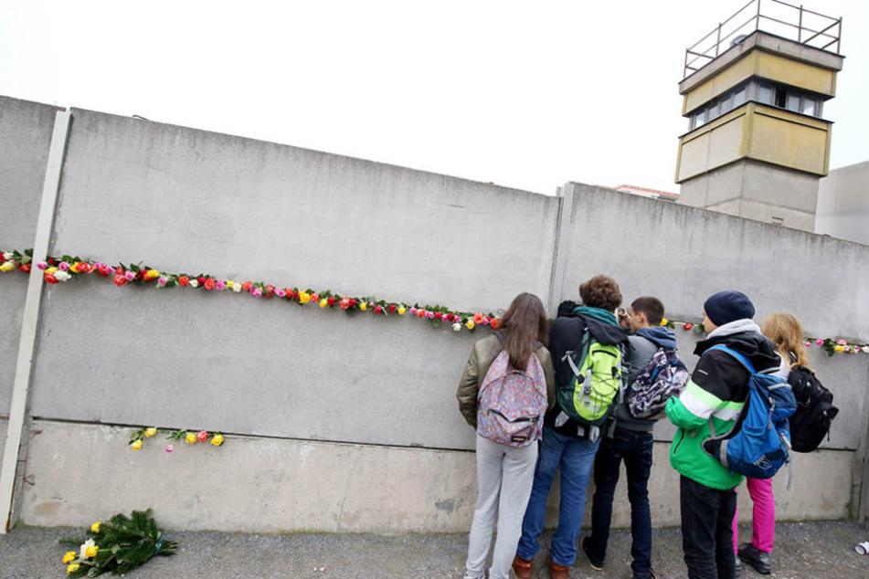 Jugendliche stecken an der Mauergedenkstätte an der Bernauer Straße zwischen die Mauersegmente und blicken durch die Sperranlagen.