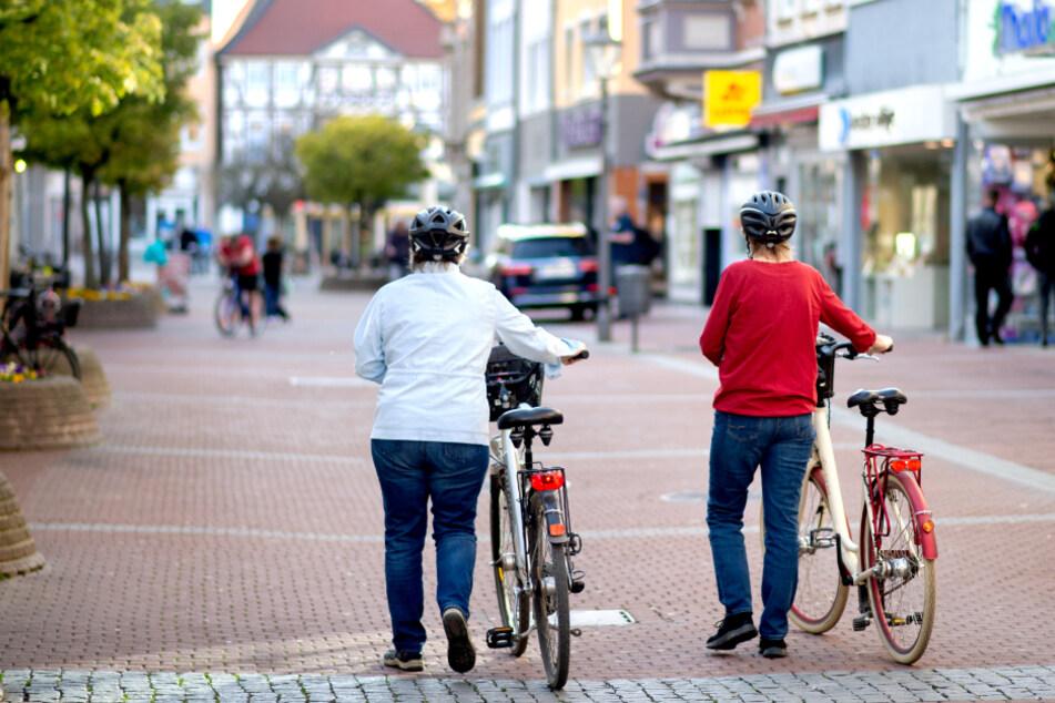 Zwei Frauen gehen mit ihren Fahrrädern durch die fast menschenleere Innenstadt.