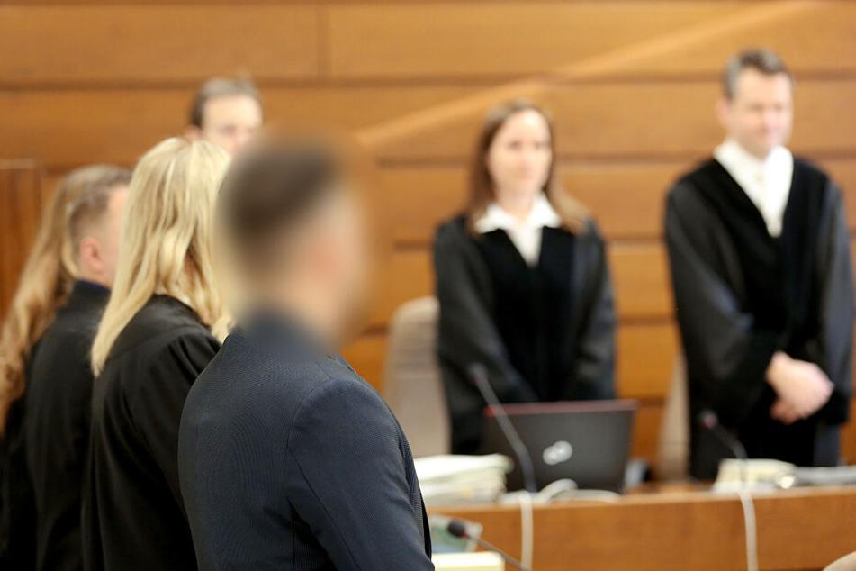 Die beiden angeklagten Journalisten (l) und ihre Anwälte stehen im Saal des Landgerichts, während die Richter auf ihren Plätzen stehen.