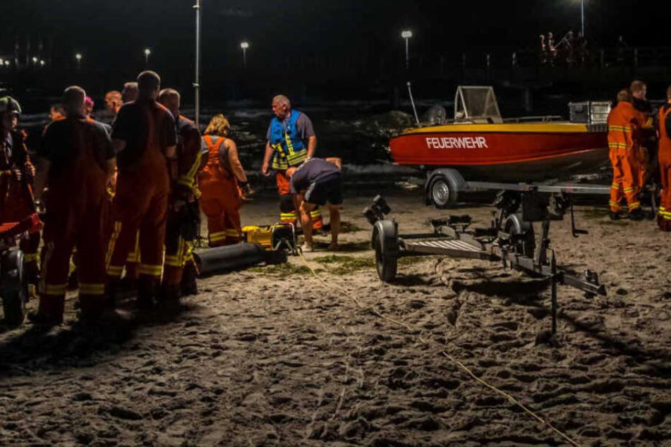 Rettungskräfte planen an einem Ostseestrand ihren Einsatz.