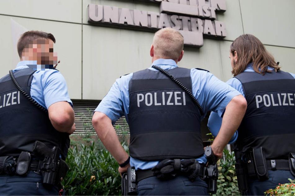 Drei Polizisten stehen vor dem Oberlandesgericht in Frankfurt am Main (Archivbild).