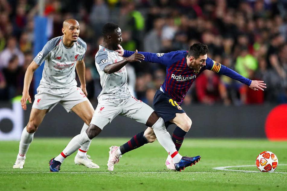 Barca-Superstar Lionel Messi (r.) wird von Liverpools spielstarkem Mittelfeldmann Naby Keita (M.) attackiert, der kurz darauf verletzt vom Feld musste.