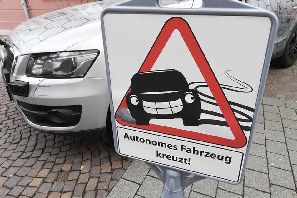 """""""Autonomes Fahrzeug kreuzt!"""" - Ein Schild macht auf das Forschungsfahrzeug """"Cocar"""" für autonomes Fahren aufmerksam."""