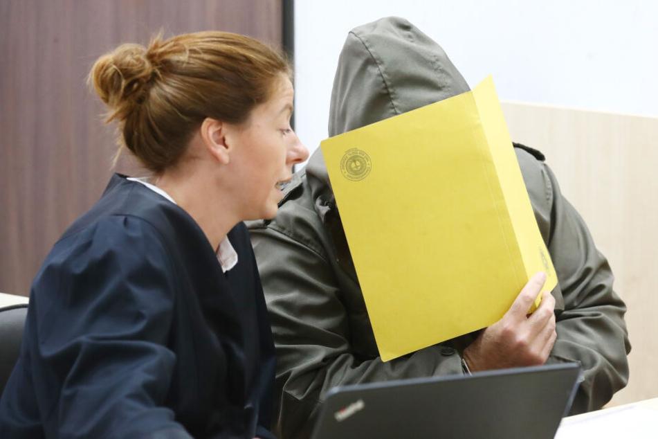 Zum Prozessauftakt versteckte sich der Angeklagte hinter einem Aktenordner.
