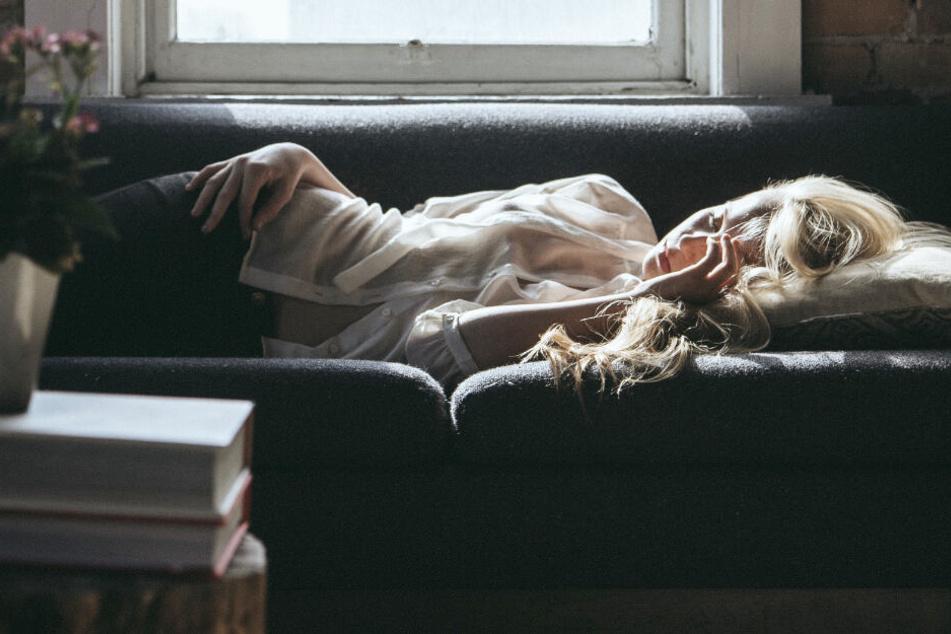 Eine junge Frau schläft auf einer Couch. (Symbolbild)
