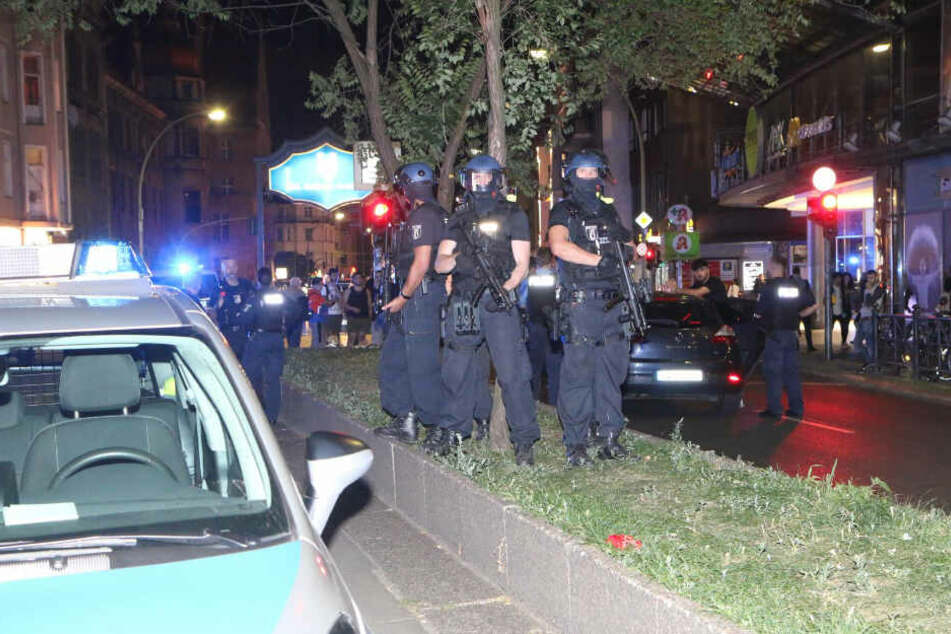 Polizisten stehen auf dem begrünten Mittelstreifen der Karl-Marx-Straße.
