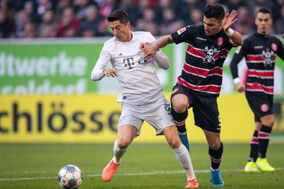Robert Lewandowski (l) vom FC Bayern und Düsseldorfs Kaah Ayhan kämpfen um den Ball.