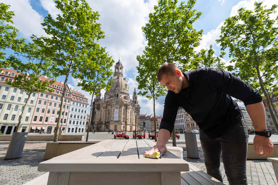 Ein Mitarbeiter eines Restaurants auf dem Neumarkt vor der Frauenkirche wischt einen Tisch ab. Ab morgen darf hier wieder geöffnet werden.