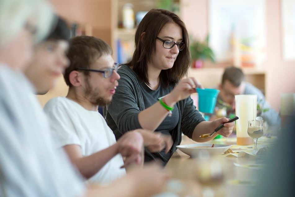 Beim gemeinsamen Abendbrot hilft eine FSJlerin im Wohnheim für Menschen mit Behinderung.