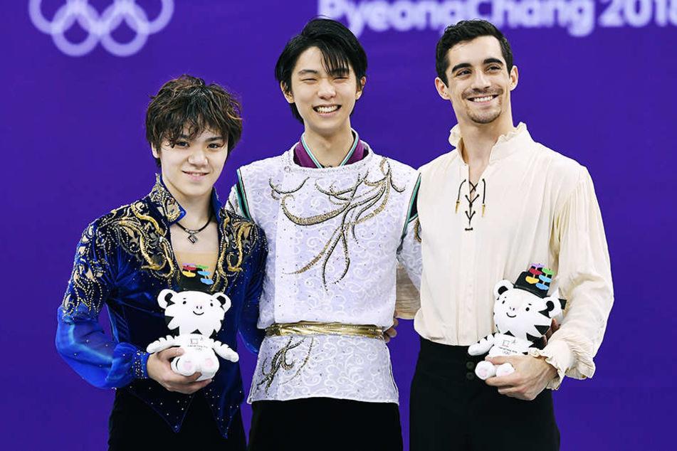 Olympiasieger Yuzuru Hanyu (M), der Zweitplazierte Shoma Uno (l), beide aus Japan und der Dritte, Javier Fernandez aus Spanien, lächeln bei der Siegerehrung.