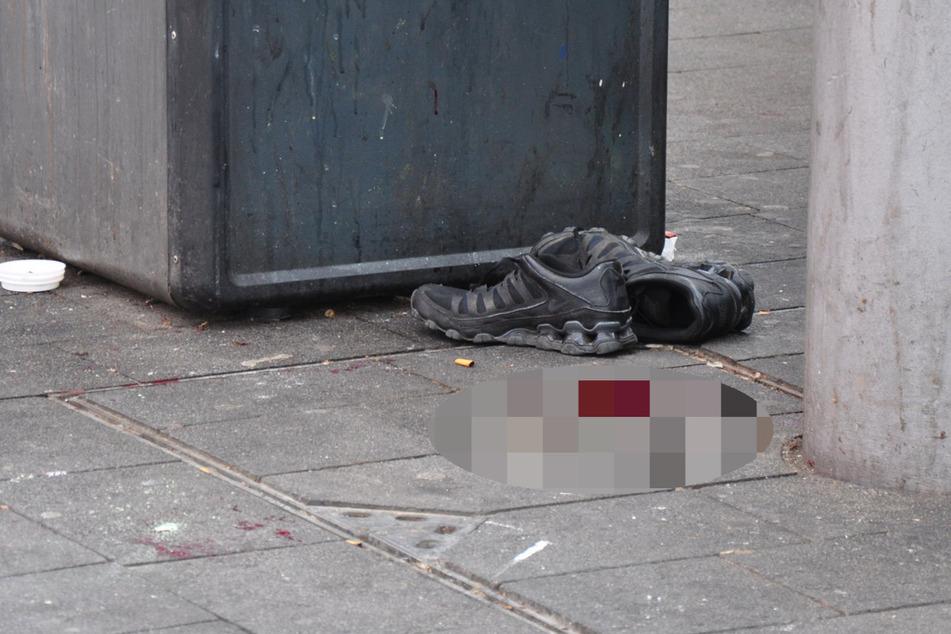 Ein Paar Schuhe steht neben einer Blutlache am Tatort.