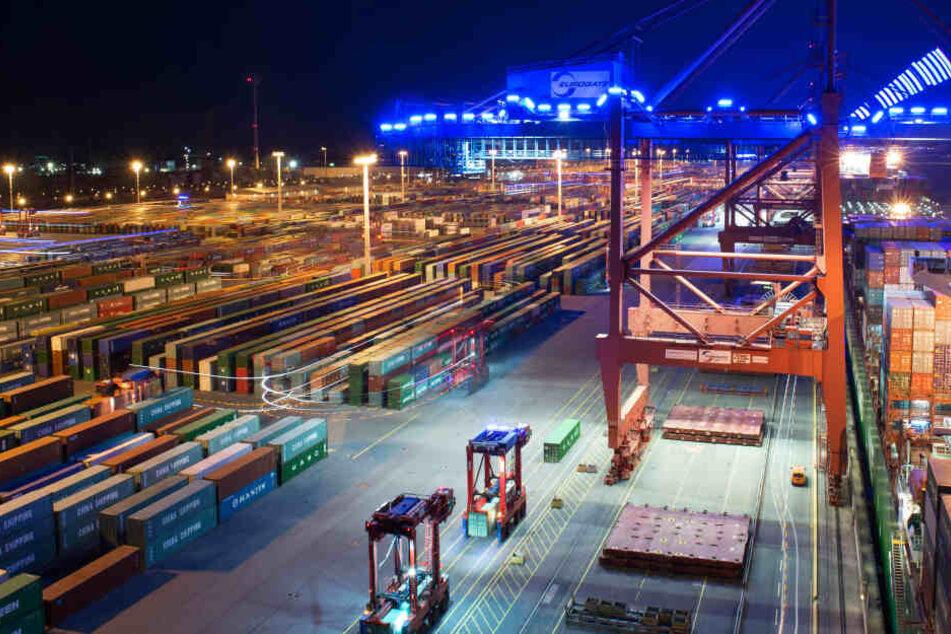"""Zahlreiche """"Van Carrier"""" fahren in der Nacht mit blauen Leuchtstoffröhren im Container-Terminal Eurogate in Hamburg umher."""