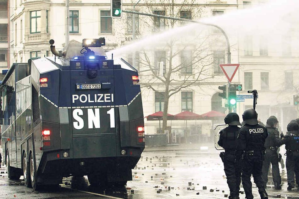"""Leipzig im Dezember 2015: Ein Wasserwerfer ist auf Demonstranten gerichtet, die gegen """"Die Rechte"""" demonstrieren."""