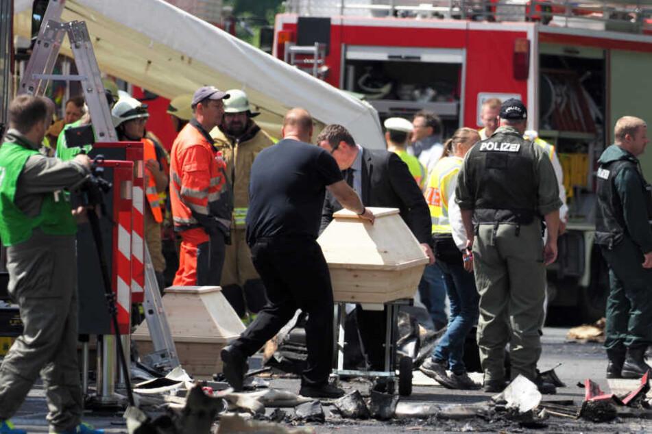 Bestatter bringen zwei Holzsärge an die Unfallstelle auf der Autobahn A9.
