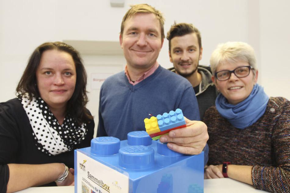 Jana Richter-Wehnert von der SBW Vogtlandkreis GmbH, Projektinitiator Rico Kusche, Bürgerbüro-Mitarbeiter David Biller und Behindertenbeauftragte Heidi Seeling (v.l.) mit einer Sammelbox für Legosteine.