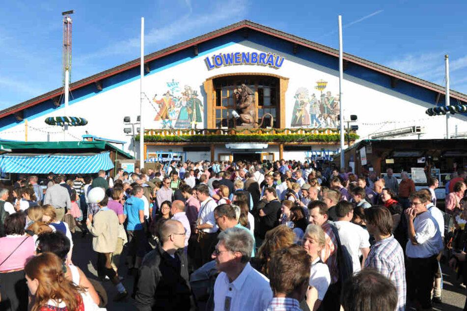 Oktoberfestbesucher stehen vor der Löwenbräu-Festhalle auf der Wiesn.