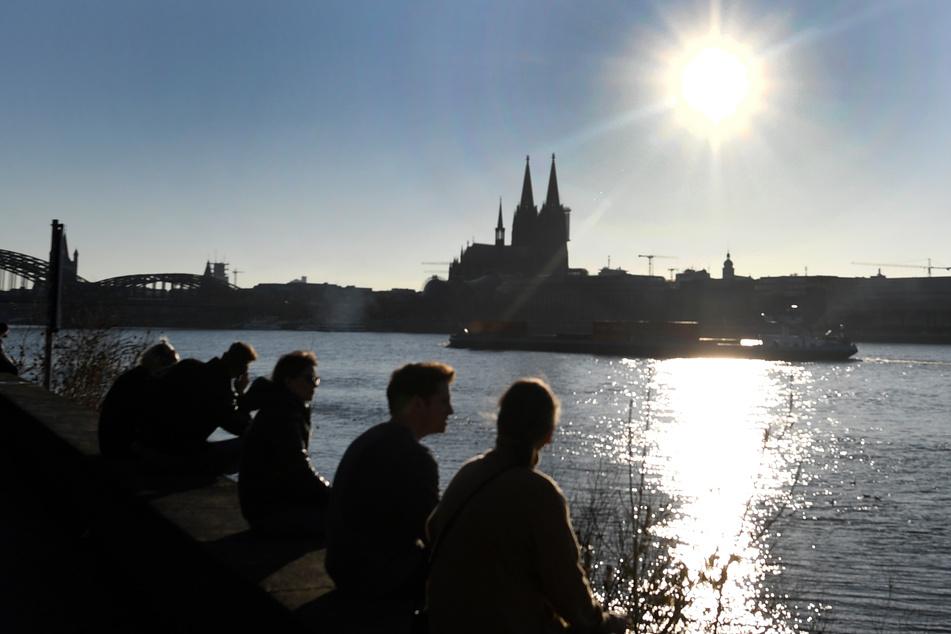 Menschen in Köln genießen die Sonne am Rhein. Bis zum Wochenende soll das Wetter in NRW heiter und warm bleiben.