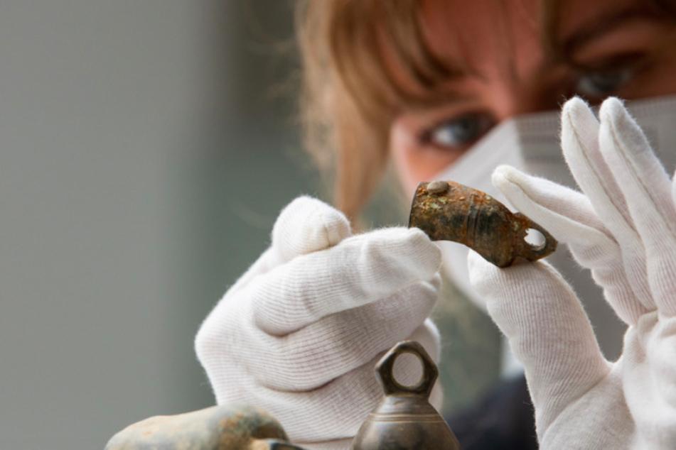 Ayla Heeg von der Stadtarchäologie betrachtet das Fragment einer Glocke. Diese gehört zu Ausgrabungsfunden aus der Römerzeit in Augsburg.