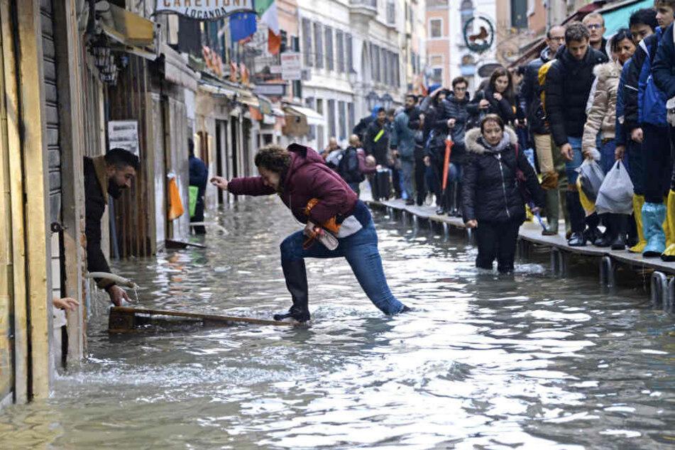 Hochwasseralarm in Venedig! Eine Frau versucht, eine überflutete Straße zu überqueren, während Menschen auf einer Gerüstbrücke laufen.