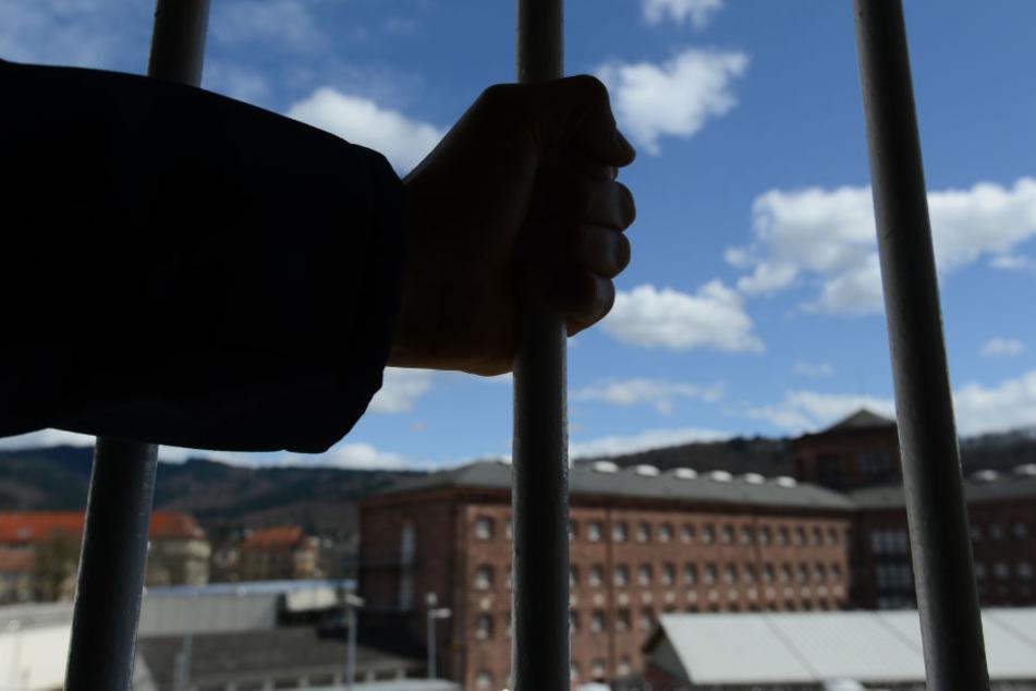 Ein Mann steht in der Justizvollzugsanstalt in Freiburg vor einem vergitterten Fenster. (Symbolbild)