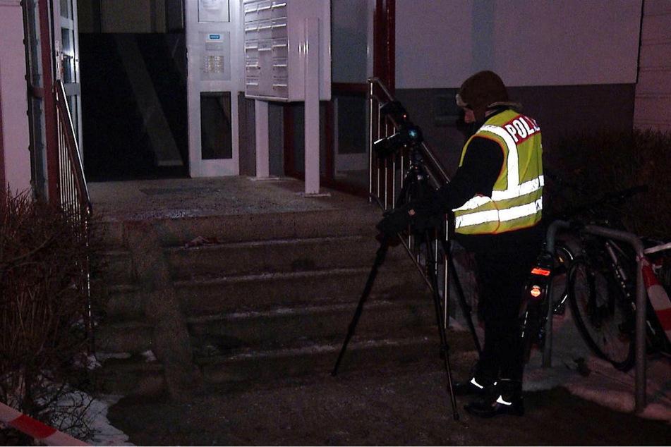 Ein Kriminaltechniker der Polizei macht Aufnahmen von den Blutspuren im Eingangsbereich des Mietshauses in Berlin-Lichtenberg.