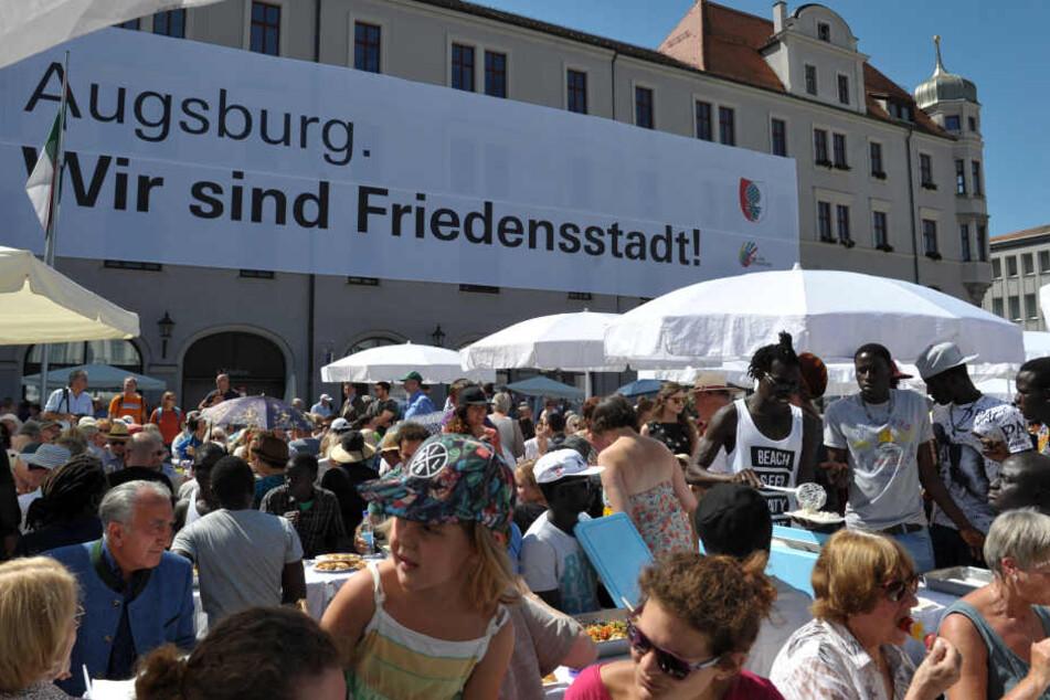 Besucher des Friedensfestes versammeln sich am zu einer gemeinsamen Friedenstafel. (Archivbild)
