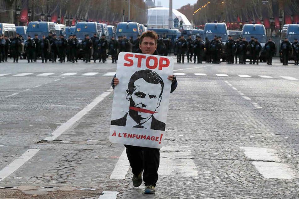 Der Demonstrant trägt ein Plakat mit dem Abbild des französischen Präsidenten auf der Champs Elysees, im Hintergrund stehen Polizisten. Frankreichs Regierung fürchtet weitere Ausschreitungen in Paris und will mit einem massiven Aufgebot von Sicherheitskrä