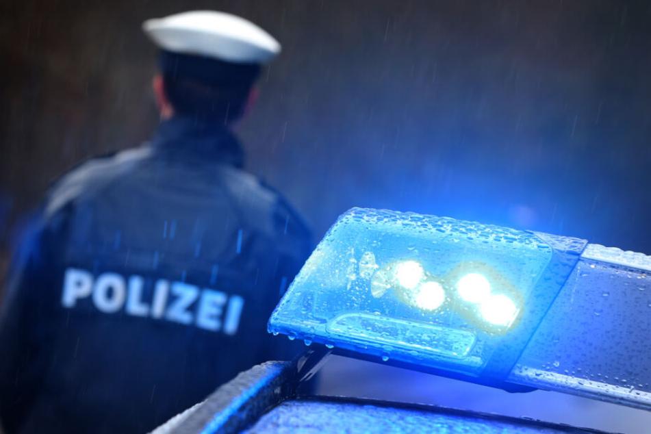 Ein Polizist steht im Regen neben seinem Polizeifahrzeug. (Symbolbild)