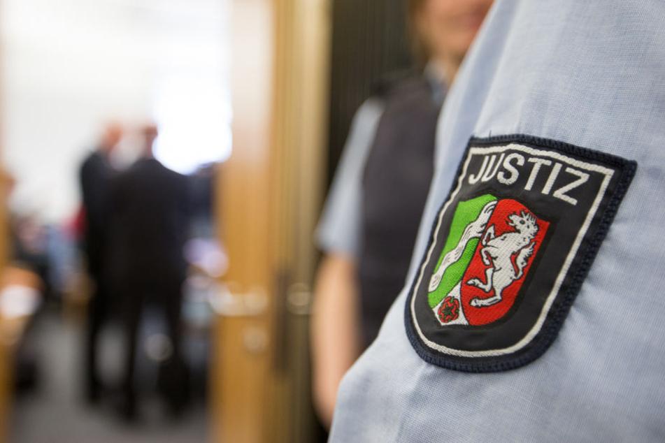 Ein Justizbeamter steht beim Prozessauftakt nach dem Tod eines Streitschlichters vor dem Sitzungssaal. Zwei Angeklagte müssen sich wegen fahrlässiger Tötung verantworten.