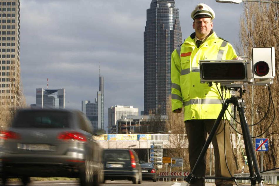 Ein Polizist stehr am Ende einer Autobahn in Frankfurt neben dem Scanner des Automatischen Kennzeichenlesesystems.