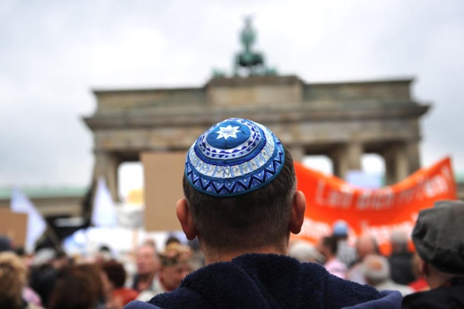 Teilnehmer der Kundgebung «Steh auf! Nie wieder Judenhass!» des Zentralrats der Juden in Deutschland stehen vor dem Brandenburger Tor in Berlin.
