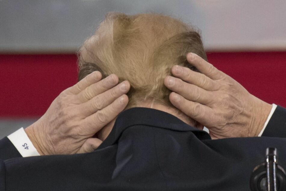 Donald Trump versucht seine kahle Stelle am Hinterkopf zu verstecken.