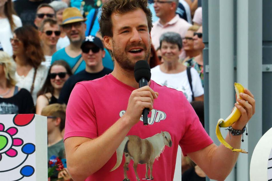 """Luke Mockridge, Comedian, steht mit einer Banane in der Hand auf der Bühne des """"ZDF-Fernsehgarten""""."""