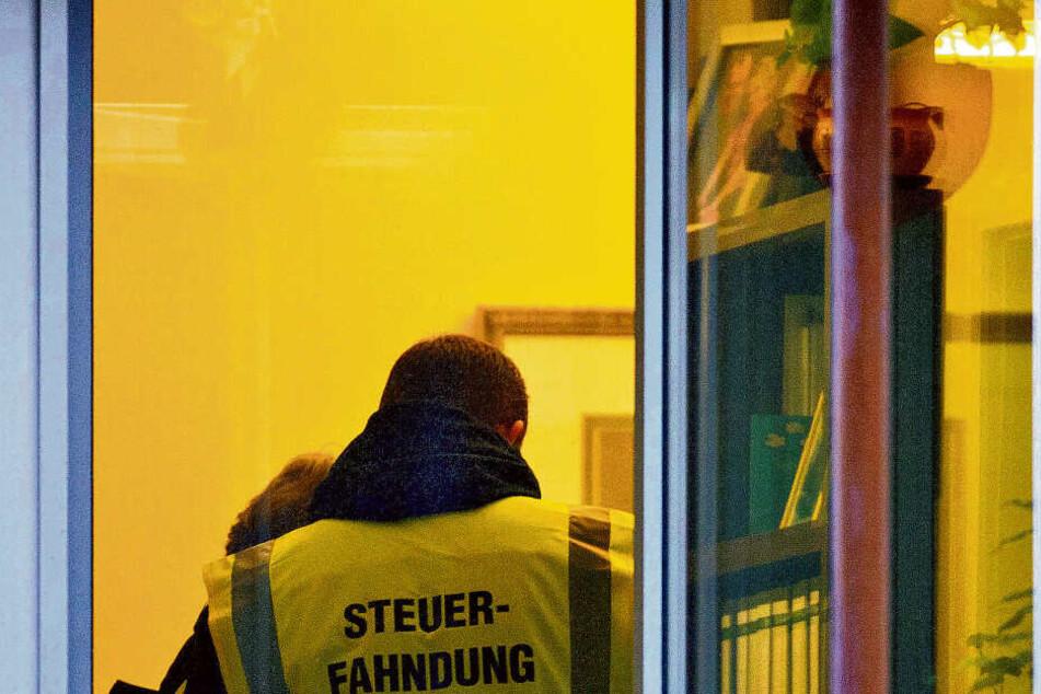 Ein Steuerfahnder, fotografiert bei einer Hausdurchsuchung.