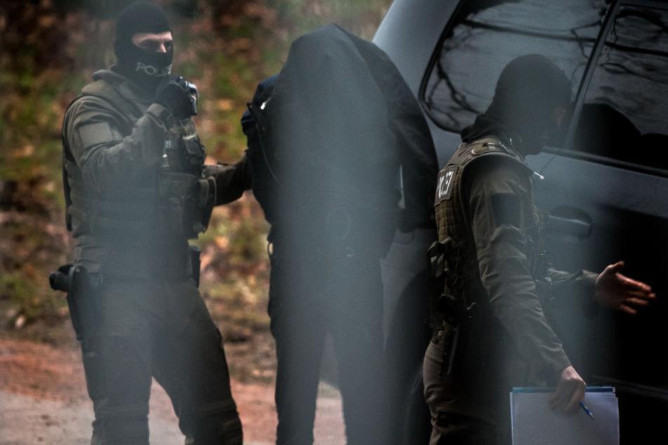 Der Tatverdächtige wird auf dem Gelände des Bundesgerichtshof in Karlsruhe von Polizeieinheiten aus einem Fahrzeug geführt.