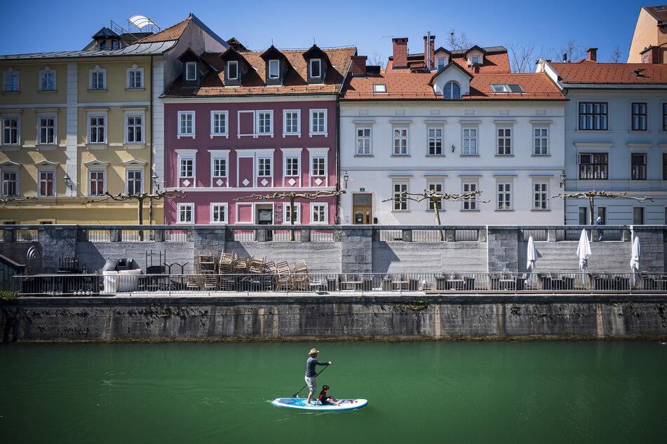 Ein Stehpaddler fährt mit einem Board, auf dem außerdem ein Junge sitzt, über die Ljubljanica in Slowenien.