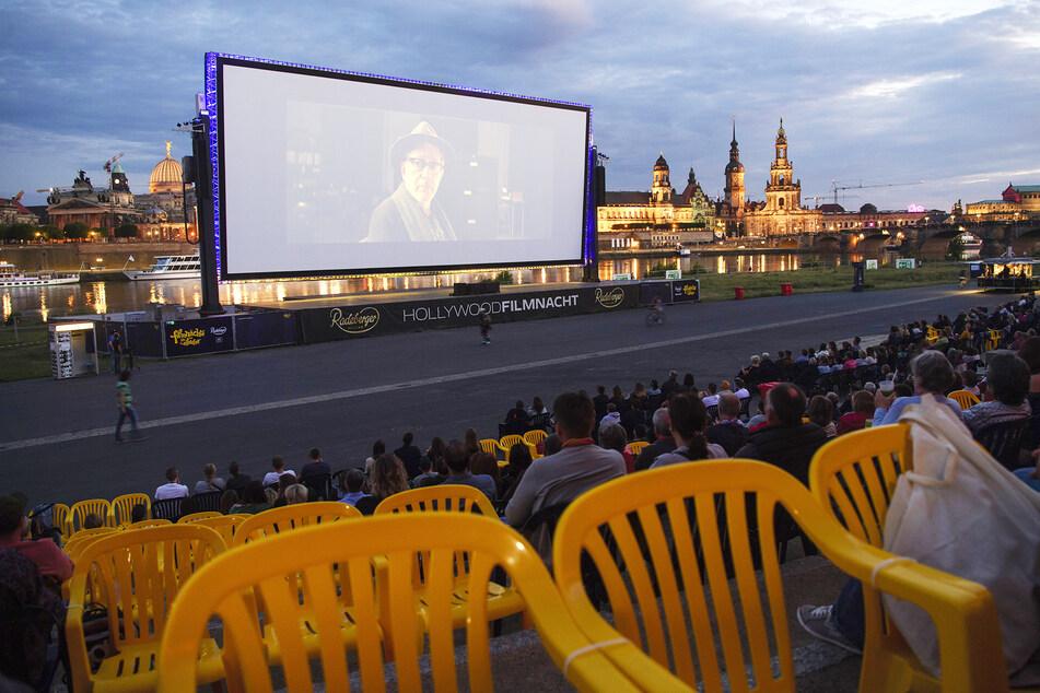 """Zahlreiche Gäste der """"Filmnächte am Elbufer"""" sitzen vor der Kulisse der Dresdner Altstadt und schauen auf eine Kinoleinwand. Das Freiluftkino startete am Donnerstag auch in Zeiten des Coronavirus mit dem Film """"Bohemian Rhapsody""""."""