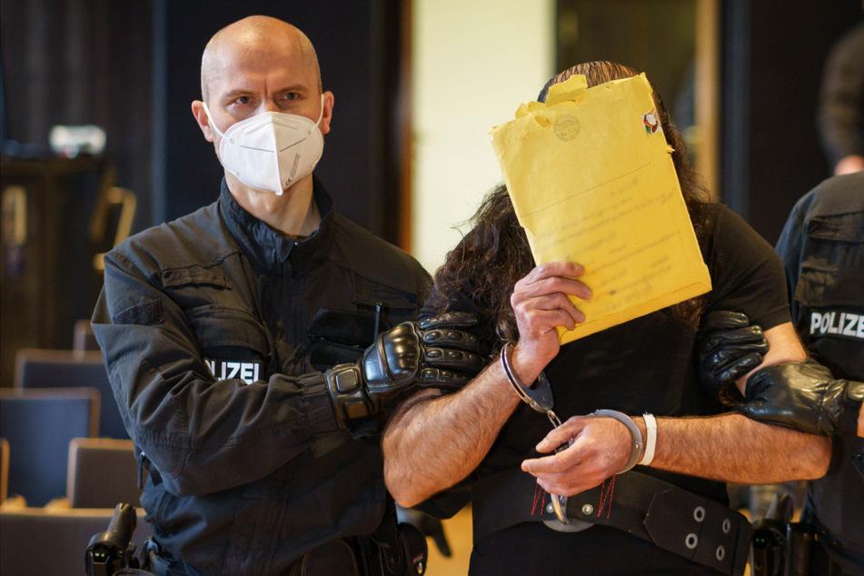 Der 46-jährige Angeklagte wird von Polizisten in Handschellen zur Anklagebank geführt.