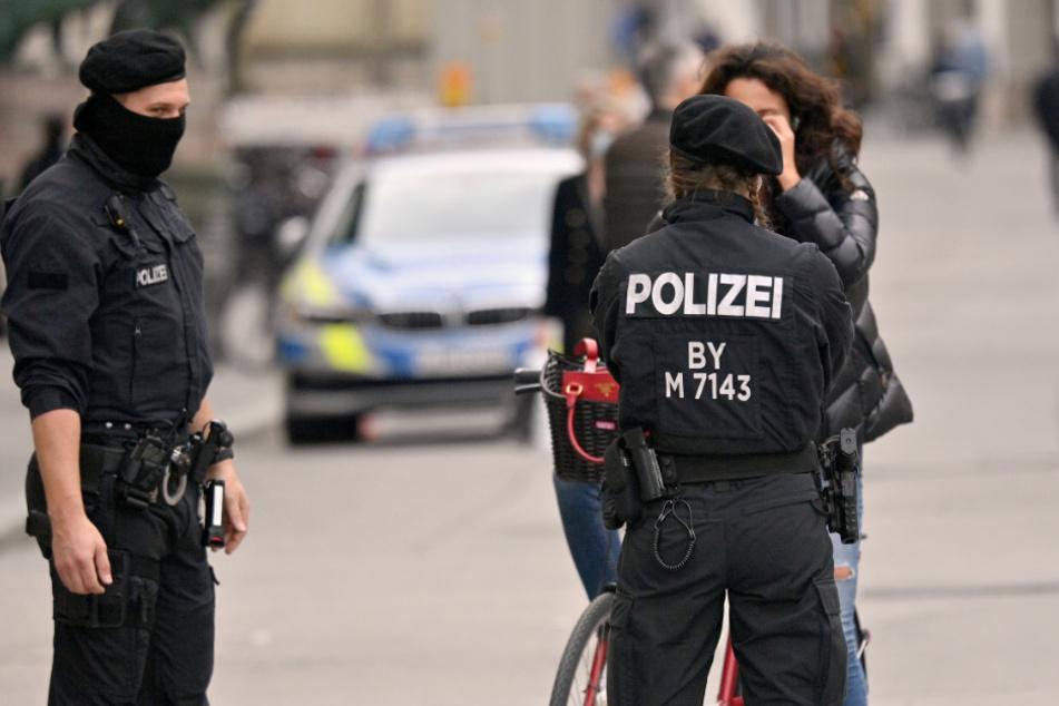 Polizisten kontrollieren in der Innenstadt die Einhaltung der Maskenpflicht bei einer Radfahrerin. (Symbolbild)