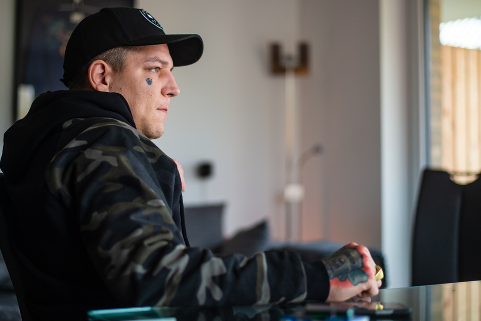 Marcel Eris (32) sitzt während eines Interviews in seiner Wohnung.