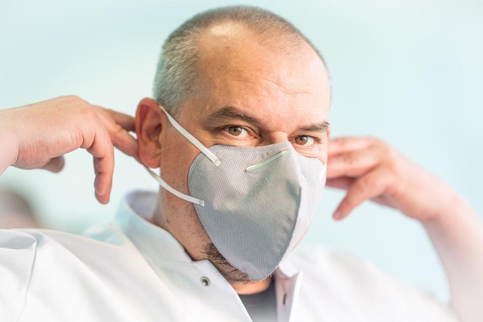 Geschäftsführer Rico Genau (49) zeigt eine keimtötende Maske.